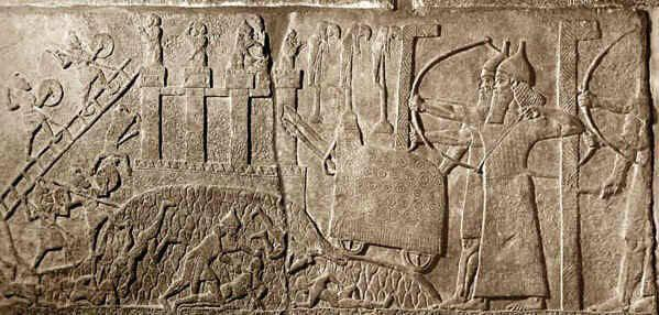 Εικ. 4. Εισβολή στα τείχη της Λαχίς με Ασσύριους τοξότες και πολιορκητικό κριό. Ανασκολοπισμένοι αιχμάλωτοι απεικονίζονται στο κέντρο της εικόνας. Η πρακτική του τρόμου αποτελεί ένα ισχυρό όπλο στα χέρια των Ασσυρίων  (λεπτομέρεια από το ανάγλυφο της Λαχίς). Βρετανικό Μουσείο, Λονδίνο.